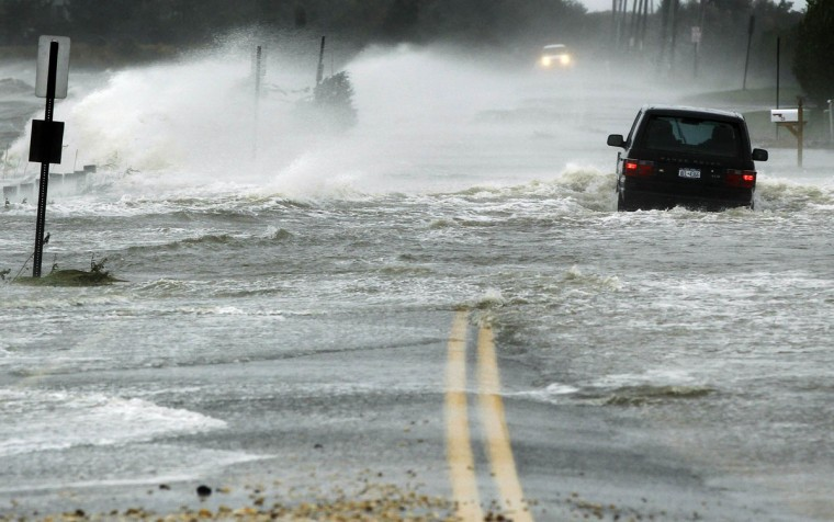 October 29, 2012: A car drives through water driven onto a roadway by Hurricane Sandy in Southampton, New York. (Lucas Jackson/Reuters)