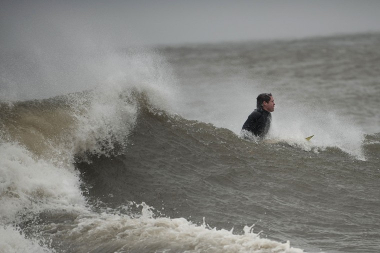 October 29, 2012: A surfer catches a wave along Coney Island in New York. (Keith Bedford/Reuters)