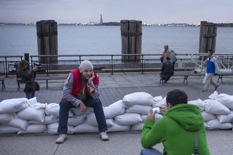 October 28, 2012: The Statue of Liberty is seen in the background as tourists from Russia pose for pictures on top of sand bags protecting Battery Park in Lower Manhattan, New York. (Adrees Latif/Reuters)