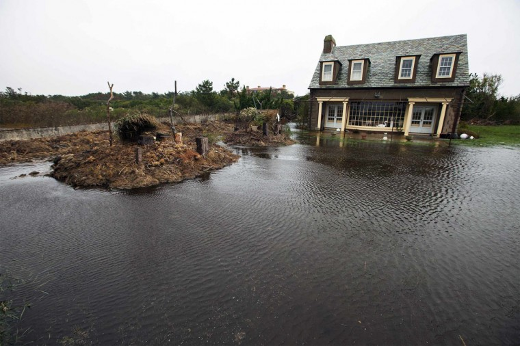 October 29, 2012: A house stands in the center of a yard flooded by water driven inland by Hurricane Sandy in Southampton, New York. (Lucas Jackson/Reuters)