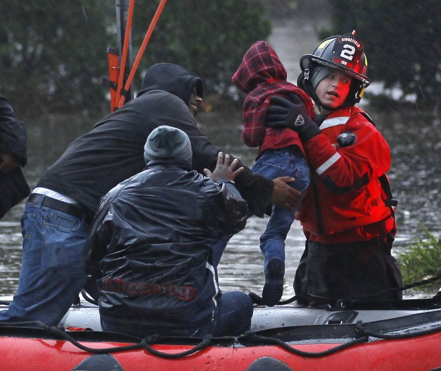 October 30, 2012: Residents, including a young child, are rescued by emergency personnel from flood waters brought on by Hurricane Sandy in Little Ferry, New Jersey. (Adam Hunger/Reuters)