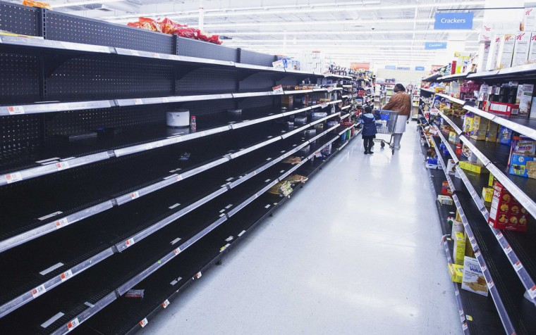 October 28, 2012: A woman and child walk through an aisle, emptied in preparation for Hurricane Sandy, in a Wal-Mart store in Riverhead, New York. (Lucas Jackson/Reuters)