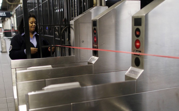 October 28, 2012: A Metropolitan Transportation Authority (MTA) employee tapes off the turnstiles to bar access to the subway in New York. (Carlo Allegri/Reuters)