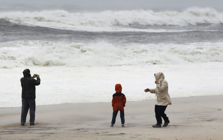 October 29, 2012: Residents from Long Island stand on the beach to take photographs of the waves churned up by Hurricane Sandy in Southampton, New York. (Lucas Jackson/Reuters)