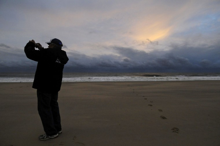 October 30, 2012: A man takes a picture of calm seas and sun-dappled clouds in the aftermath of Hurricane Sandy, at sunrise on Rehoboth Beach, Delaware. (Jonathan Ernst/Reuters)