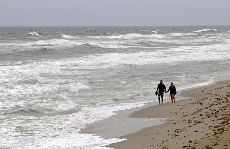 October 25, 2012: A couple walks on the beach after lifeguards closed the area for swimming as winds from Hurricane Sandy begin to affect weather in Deerfield Beach, Florida. (Joe Skipper/Reuters)