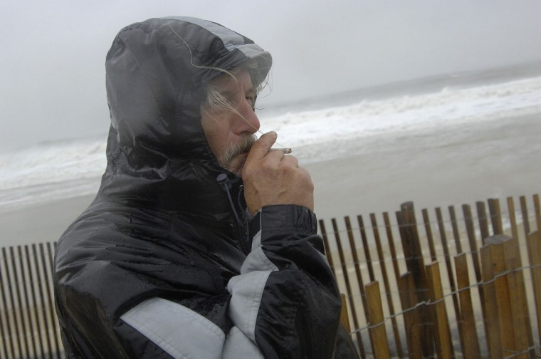 October 29, 2012: Local resident Roger Vanwart smokes a cigarette as he watches waves batter the beach at Dewey Beach, Delaware. (Jonathan Ernst/Reuters)