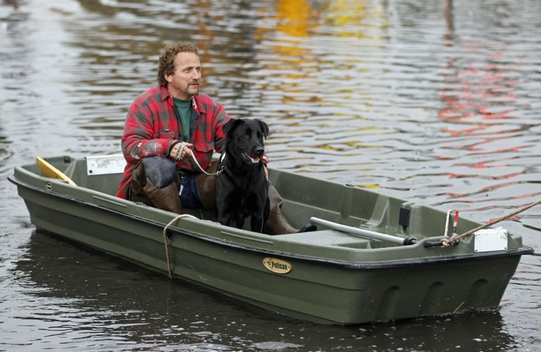 October 30, 2012: Ray Cilli and his dog Woubie are rescued from flood waters brought on by Hurricane Sandy in Little Ferry, New Jersey. (Adam Hunger/Reuters)
