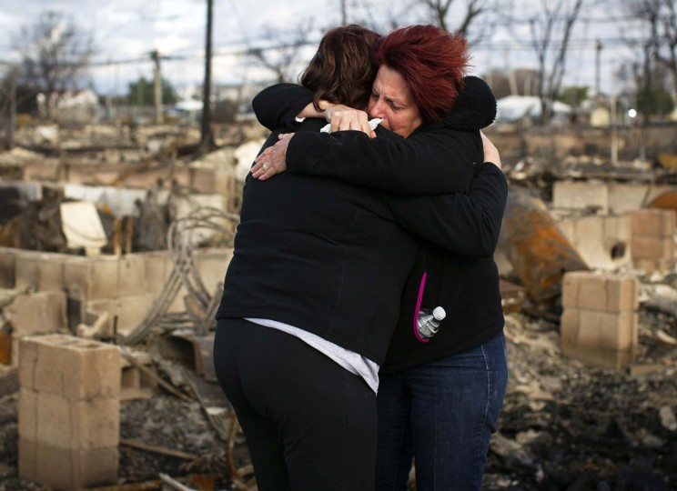 Neighbors Lucille Dwyer, right, and Linda Strong embrace after looking through the wreckage of their homes devastated by fire and the effects of Hurricane Sandy in the Breezy Point section of Queens in New York. (Shannon Stapleton/Reuters)
