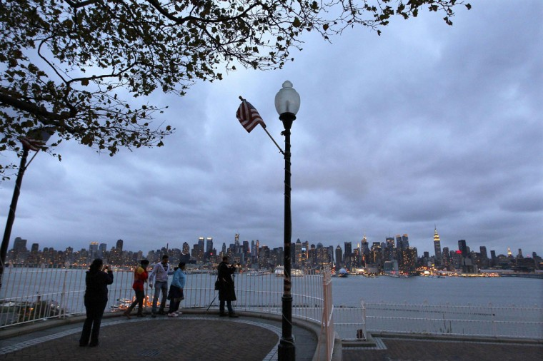 Gray skies hover over the skyline of New York as people photograph the city from a park along the Hudson River in Weehawken, New Jersey, October 28, 2012. Tens of millions of East Coast residents scrambled on Sunday to prepare for Hurricane Sandy, which could make landfall as the largest storm to hit the United States, bringing battering winds, flooding and even heavy snow. (Gary Hershorn/Reuters photo)