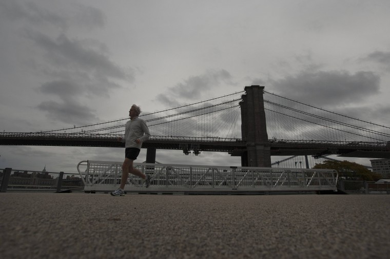 A man jogs along Brooklyn Promenade as clouds move over Brooklyn Bridge in New York. (Keith Bedford/Reuters)
