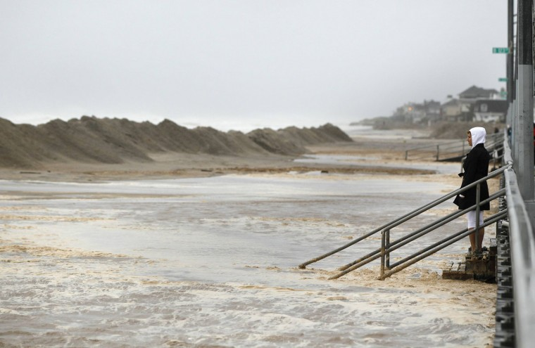 October 29, 2012: A woman watches the waves on at Beach 122nd street in the Queens borough of New York. (Shannon Stapleton/Reuters)