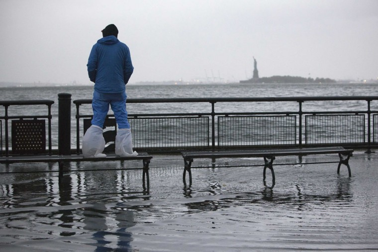October 29, 2012: A man watches the rising tides in Battery Park as Hurricane Sandy makes its approach in New York. (Andrew Kelly/Reuters)
