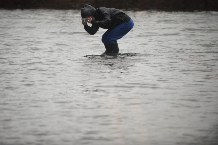 A woman takes a picture of flood waters in the Red Hook neighborhood of Brooklyn in New York