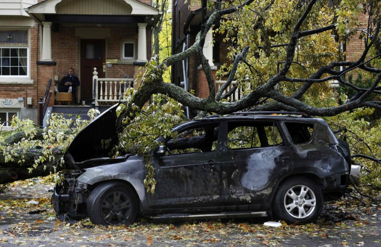 October 30, 2012: A man sits on his porch behind a car that was burned out in an electrical fire after a tree fell over a power line due to the remnants of Hurricane Sandy in Toronto. More than 100,000 Canadians were still without power on Tuesday after the huge storm Sandy toppled trees and power lines in Canada's most populous provinces, killed one person, and halted units at an Ontario refinery. (Mark Blinch/Reuters)