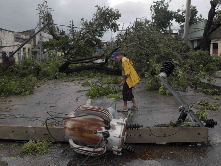 October 25, 2012: A man walks near a damaged power line in Santiago de Cuba. Hurricane Sandy grew into a major potential threat to the east coast of the United States on Thursday after hammering Cuba's second-largest city and taking aim at the Bahamas, U.S. forecasters said. (Miguel Rubiera/Cuban Government National Information Agency/AIN/Handout/Reuters)