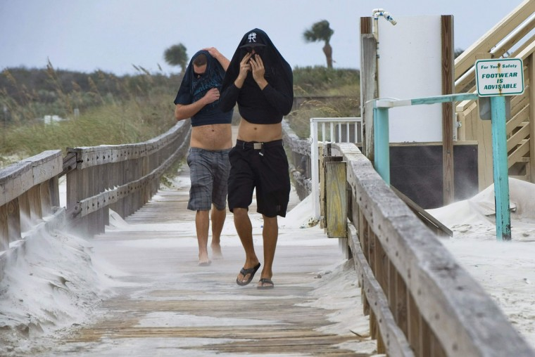 October 26, 2012: Tom Palombo (R) and Eric Huana cover themselves from sand blowing in the wind as Hurricane Sandy passes offshore at Lighthouse Point Park in Ponce Inlet, Florida. (Steve Nesius/Reuters)