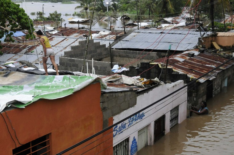 October 26, 2012: Residents are seen in the neighbourhood of Barquita, submerged in floodwaters after days of heavy rain in Santo Domingo. (Ricardo Rojas/Reuters)