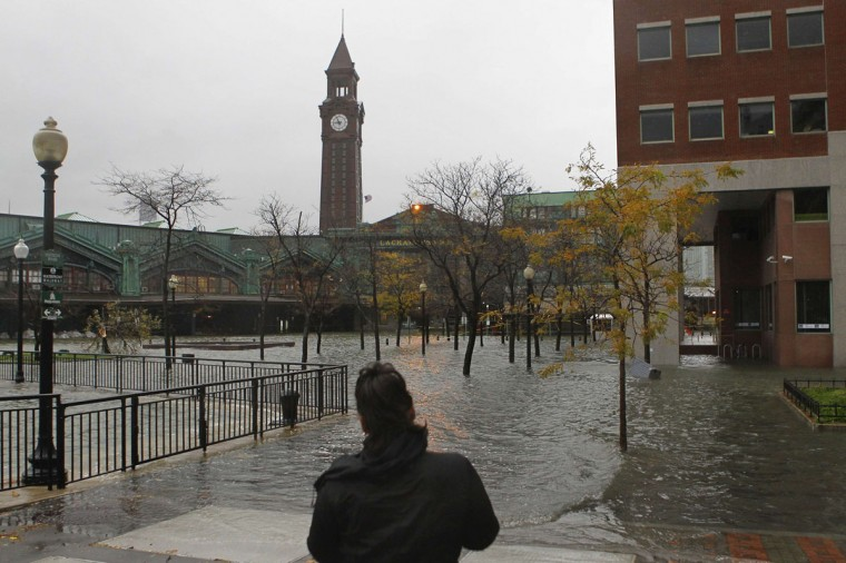 October 29, 2012: A person looks at water from the Hudson River spilling over a wall flooding the street in front of the train station in Hoboken, New Jersey. (Gary Hershorn/Reuters)