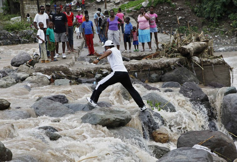 October 25, 2012: Residents of Kingston try to cross the Hope River after a bridge was washed out by Hurricane Sandy. (Gilbert Bellamy/Reuters)