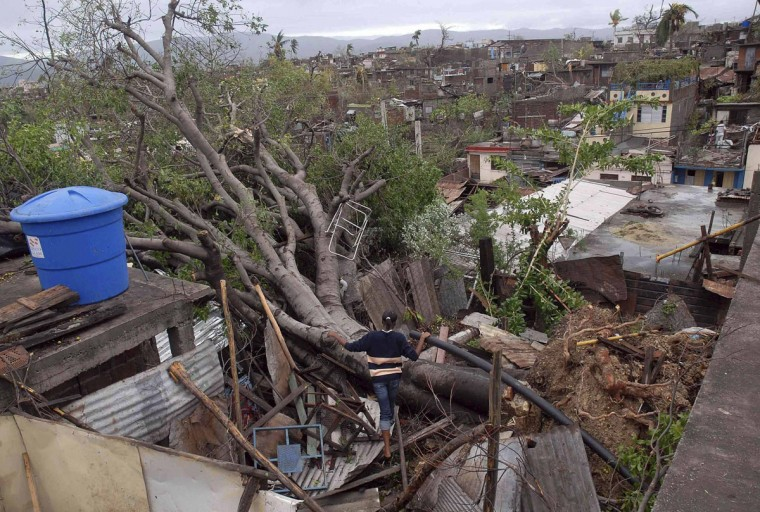 October 25, 2012: A woman looks at a fallen tree on top of her house after Hurricane Sandy hit Santiago de Cuba. (Miguel Rubiera/Cuban Government National Information Agency/AIN/Handout/Reuters)