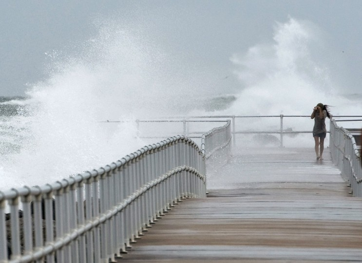 October 26, 2012: Jean Marie Brennan walks along the jetty at Lighthouse Point Park as Hurricane Sandy passes offshore in Ponce Inlet, Florida. (Steve Nesius/Reuters)
