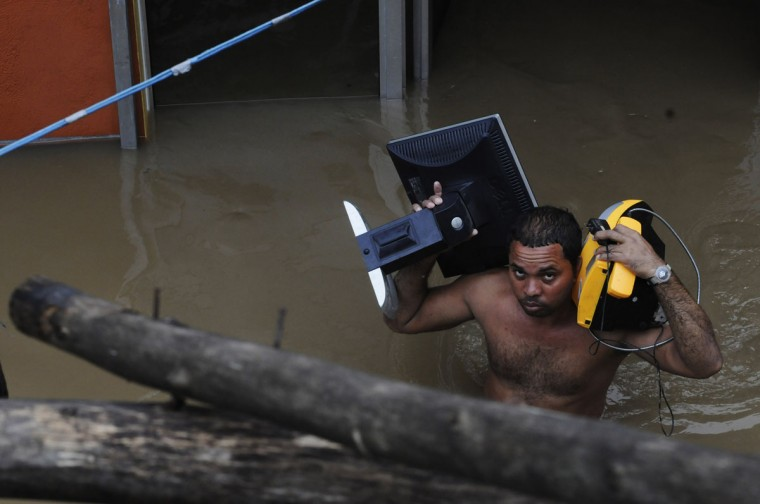 October 26, 2012: A resident carries electrical appliances as he walk in floodwaters in the neighborhood of Barquita after days of heavy rain in Santo Domingo. (Ricardo Rojas/Reuters)