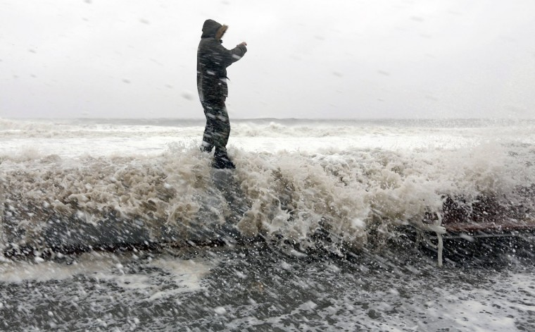 October 29, 2012: A man takes a picture while a wave crashes over the boardwalk in Ocean City, Maryland, as Hurricane Sandy intensifies. (Kevin Lamarque/Reuters)