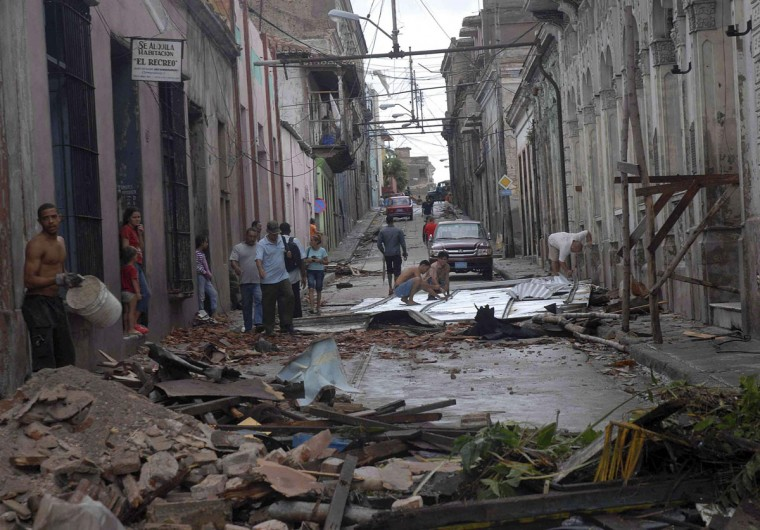 October 25, 2012: People walk near to a damaged building in Santiago de Cuba. (Miguel Rubiera Justiz/Cuban Government National Information Agency/AIN/Handout/Reuters)