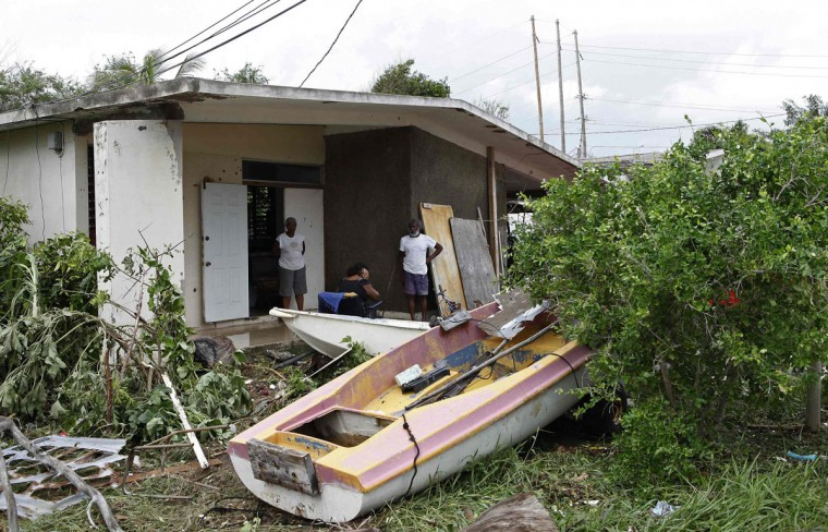 October 25, 2012: Residents of Caribbean Terrace in southern Kingston survey the damage and the boats washed up onto their lawn by Hurricane Sandy. (Gilbert Bellamy/Reuters)