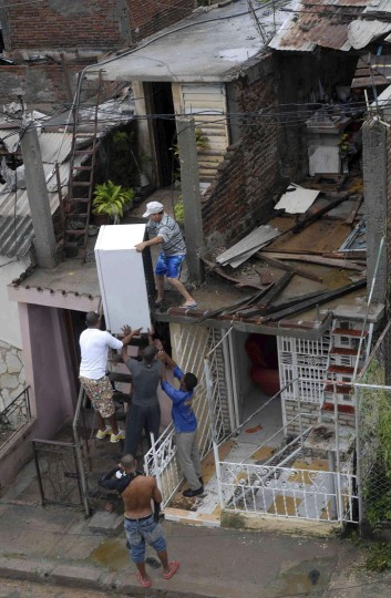 October 25, 2012: A resident (top) salvages a refrigerator from his damaged house, with the help of other men, after Hurricane Sandy hit Santiago de Cuba. (Miguel Rubiera/Cuban Government National Information Agency/AIN/Handout/Reuters)