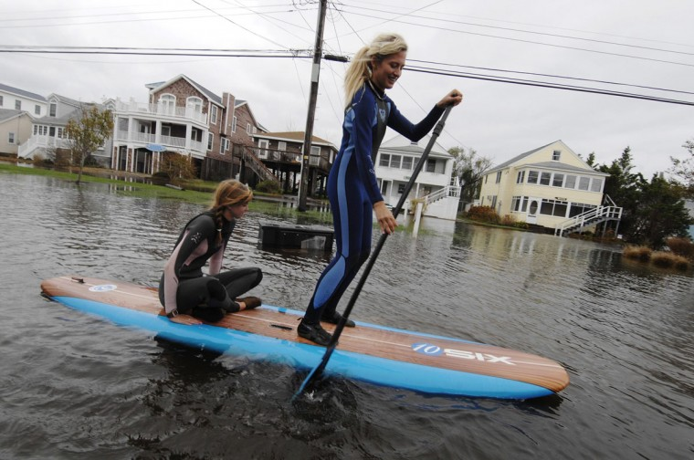 October 30, 2012: Jenna Webb (L), 18, and Zoe Jurusik, 20, paddle-board down a flooded city street in the aftermath of Hurricane Sandy in Bethany Beach, Delaware. (Jonathan Ernst/Reuters)