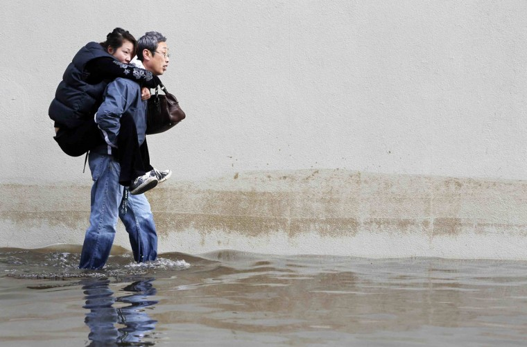 A man carries his wife through the floodwaters in Hoboken, New Jersey, October 31, 2012. (Gary Hershorn/Reuters)