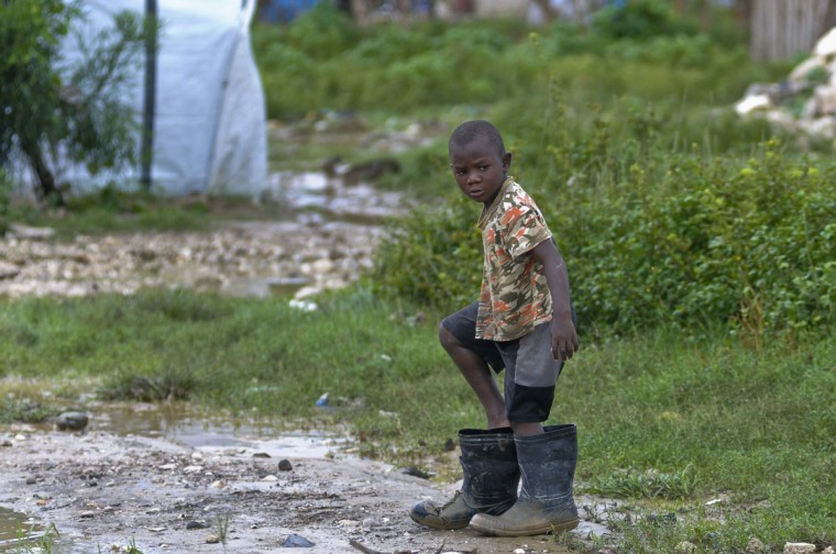 October 25, 2012: A boy puts his feet into oversized rain boots as heavy rains from Hurricane Sandy pour down in Port-au-Prince. (Swoan Parker/Reuters)