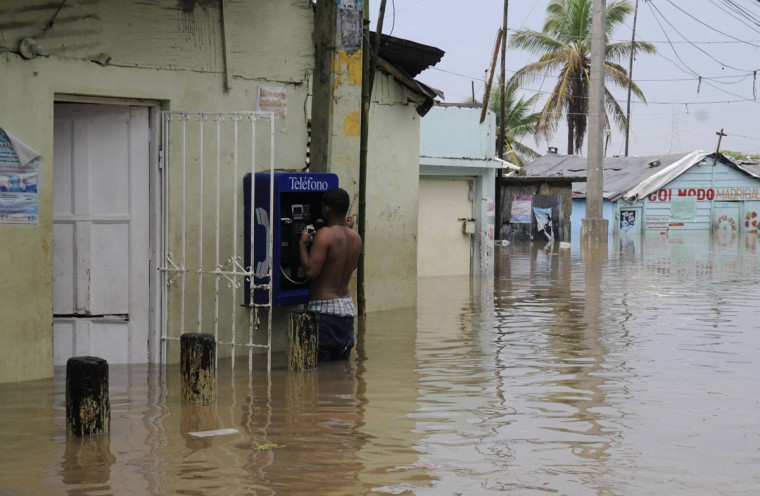 October 26, 2012: A resident talks on a public phone amidst floodwaters in the neighbourhood of Barquita, after days of heavy rain in Santo Domingo. (Ricardo Rojas/Reuters)