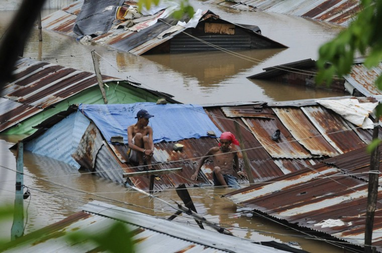 October 26, 2012: People sit on the rooftop of houses submerged in floodwaters in the neighbourhood of Barquita, after days of heavy rain in Santo Domingo. (Ricardo Rojas/Reuters)