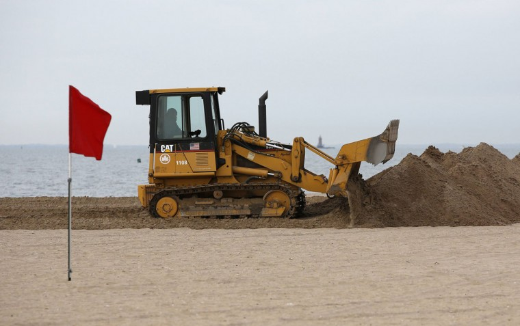 A beach closed warning flag flutters in the wind while sand is piled up in a berm before the arrival of Hurricane Sandy at Coney Island, N.Y., on October 27. (Chip East/Reuters)