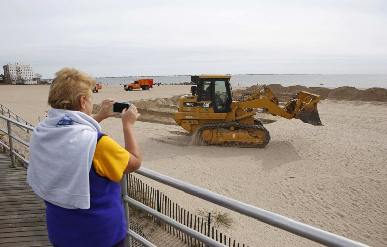 A woman stops to watch as heavy equipment is used to pile sand into protective berms before the arrival of Hurricane Sandy at Brighton Beach, N.Y. (Chip East/Reuters)