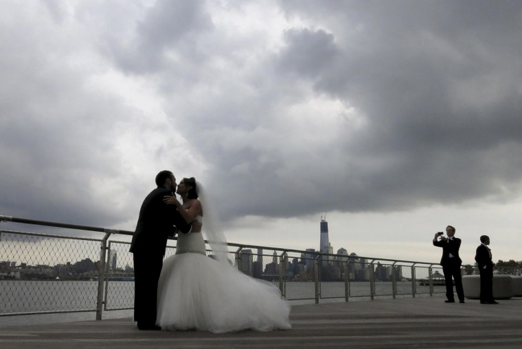 Newlyweds Kyle Legman and Michelle Sheivachman pose for their wedding pictures in a park along the Hudson River as storm clouds gather while Hurricane Sandy approaches the Eastern United States. (Gary Hershorn/Reuters)