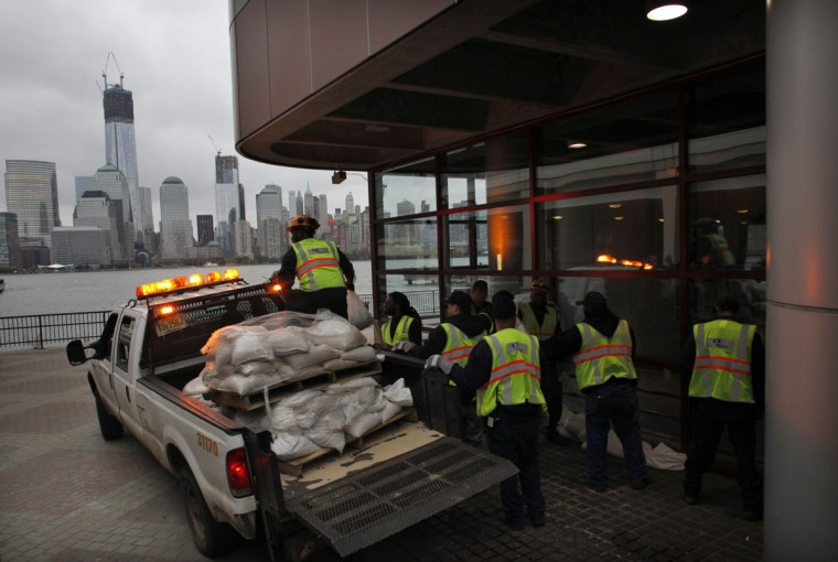 The One World Trade Center is seen as workers place sandbags outside the Exchange Place path station, located in a vulnerable part of New Jersey October 28, 2012. Tens of millions of East Coast residents scrambled on Sunday to prepare for Hurricane Sandy, which could make landfall as the largest storm to hit the United States, bringing battering winds, flooding and even heavy snow. (Eduardo Munoz/Reuters photo)