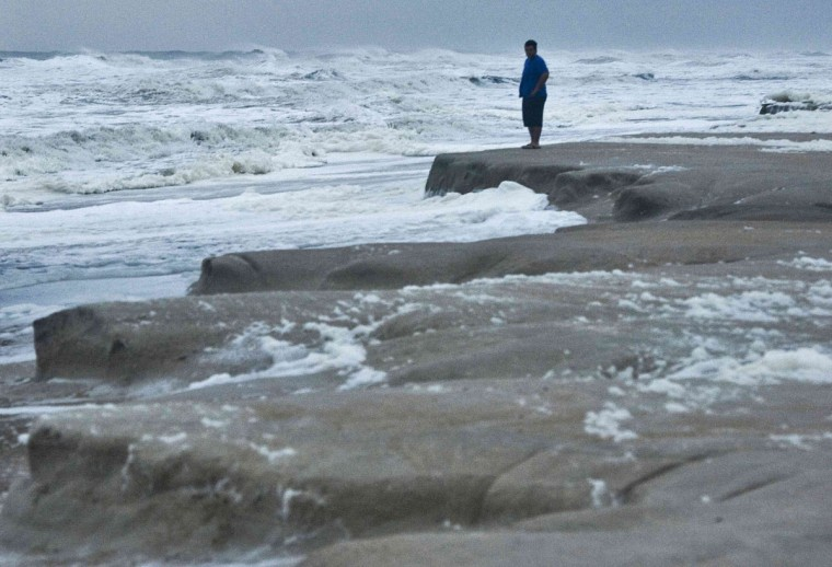 Stanley Sicinski looks on as storm surf erodes a recently refurbished shoreline in St. Augustine Beach, Fla., as Tropical Storm Sandy, downgraded overnight, passes offshore on Oct. 27, 2012. (Steve Nesius/Reuters)