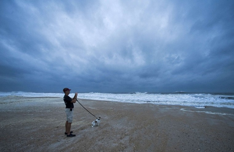 Local resident Jim Carroll photographs storm surf with his dog, Willy, in St. Augustine Beach, Fla., as Tropical Storm Sandy, briefly downgraded overnight, passes offshore. (Steve Nesius/Reuters)