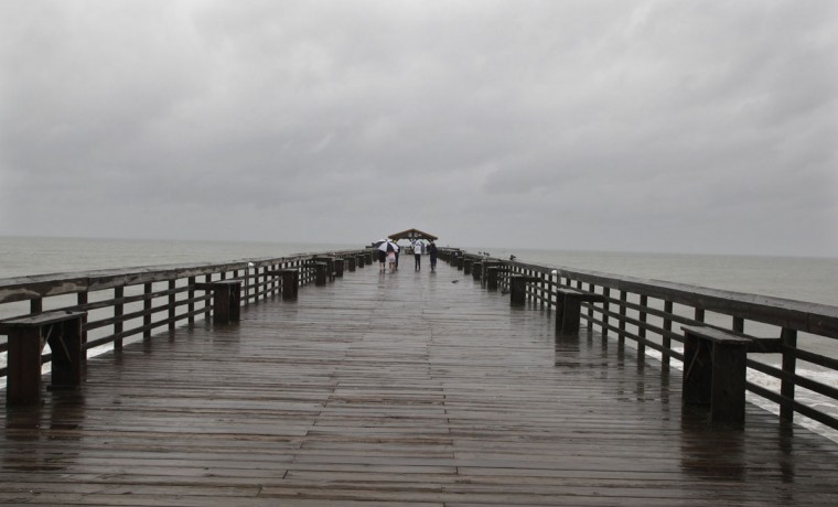 Tourists brave the wind and rain while walking the pier at Myrtle Beach State Park as Hurricane Sandy passes by offshore of South Carolina. (Randall Hill/Reuters)