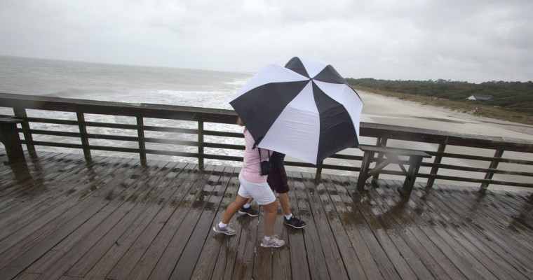 Tim and Jo Ann Griffith struggle to hold on to their umbrella as they walk the pier at Myrtle Beach State Park while Hurricane Sandy passes by offshore in South Carolina. (Randall Hill/Reuters)
