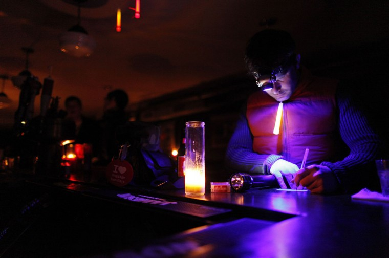 Manager Devin Vilardi wears a headlamp while doing paperwork at Professor Thom's bar, which was still serving drinks to New Yorkers despite not having power due to the aftermath of Hurricane Sandy. (Brendan McDermid/Reuters)
