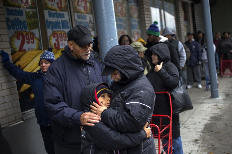 Julio and Belinda Ramos, who lost power in the aftermath of Hurricane Sandy, hold their eight-year-old son Charles as they stand in line to pick up food supplies at a grocery store in Lower Manhattan. (Adrees Latif/Reuters)
