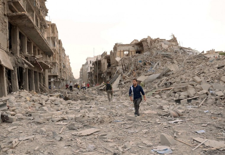 Men walk on a road amid wreckage, after blasts ripped through Aleppo's main Saadallah al-Jabari Square. Four blasts ripped through a government-controlled district close to a military officers' club in the northern Syrian city of Aleppo, killing at least 40 people and wounding more than 90 on Wednesday, opposition activists said. (George Ourfalian/Reuters)
