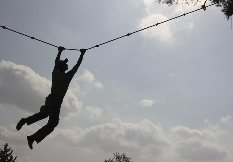 A Free Syrian Army fighter exercises on a rope during a training session at an FSA camp in the countryside of Idlib. (Giath Taha/Reuters)