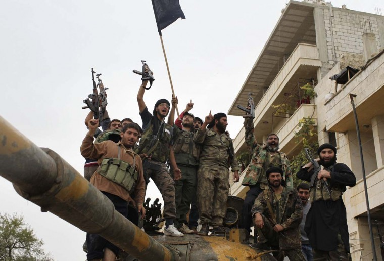 Members of the Free Syrian Army celebrate on a tank that belonged to pro-government forces after they took over the site from them early Monday in Salqin city in Idlib October 22, 2012. (Asmaa Waguih/Reuters)