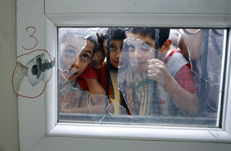Turkish boys look through a shattered window after an anti-aircraft shell fired from Syria hit a health centre across the border in the Reyhanli district of Turkey's Hatay province. (Osman Orsal/Reuters)
